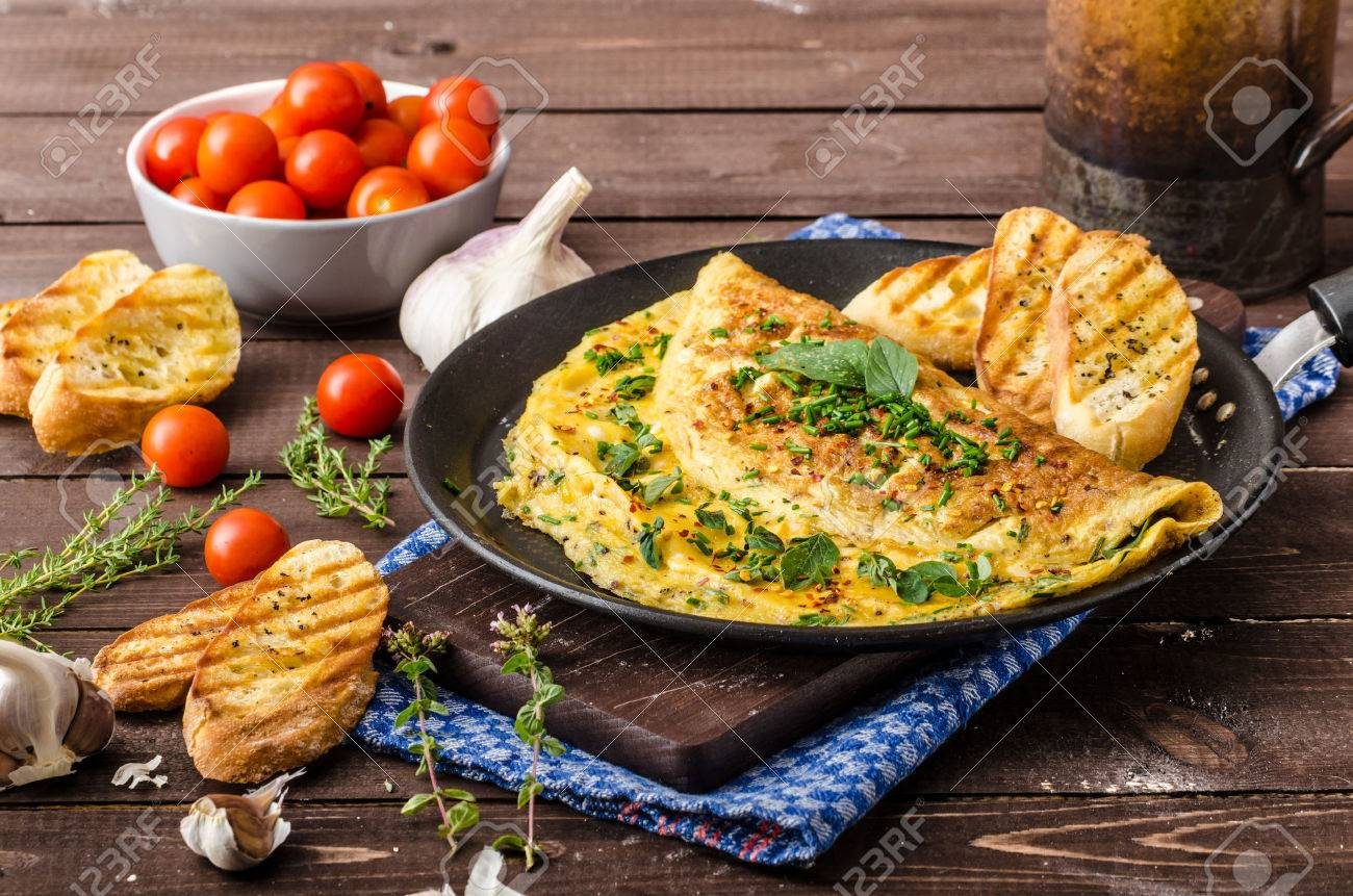 Herb omelette with chives and oregano sprinkled with chili flakes, garlic panini toasts - 43419114