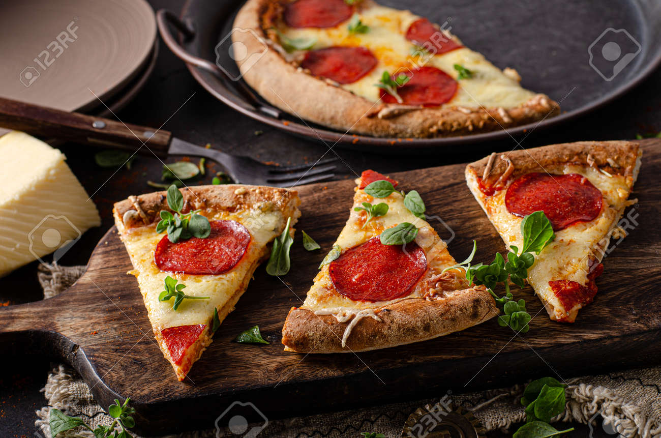 Delicious and simple pizza homemade with sharp salami and cheese corners - 145486693