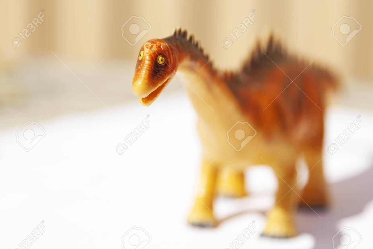 an unfortunate plastic toy dinosaur - 153245087
