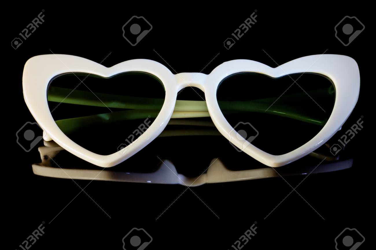 54af2c08e7 White heart shaped sunglasses on a black background. Stock Photo - 95928983