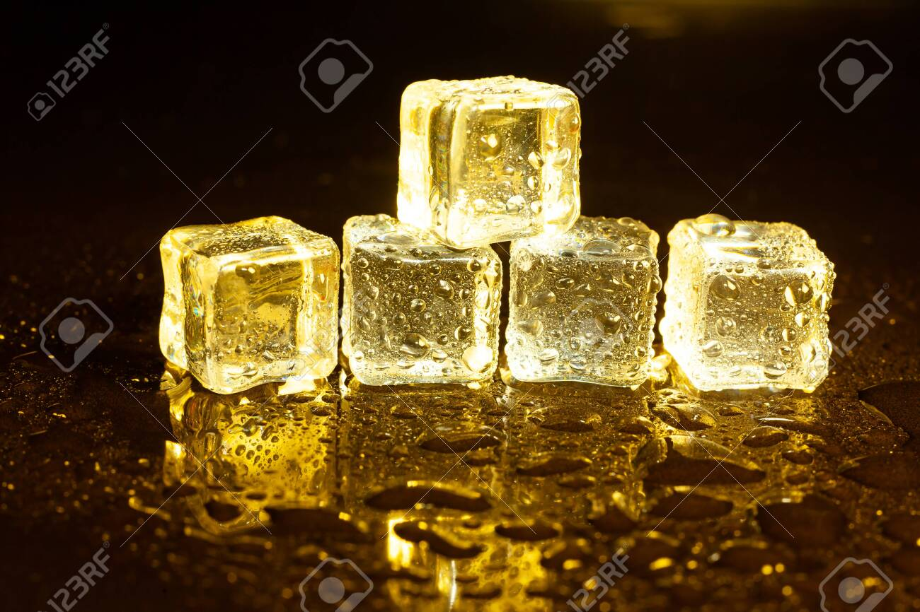 ice cubes on a reflections yellow light. - 121549396