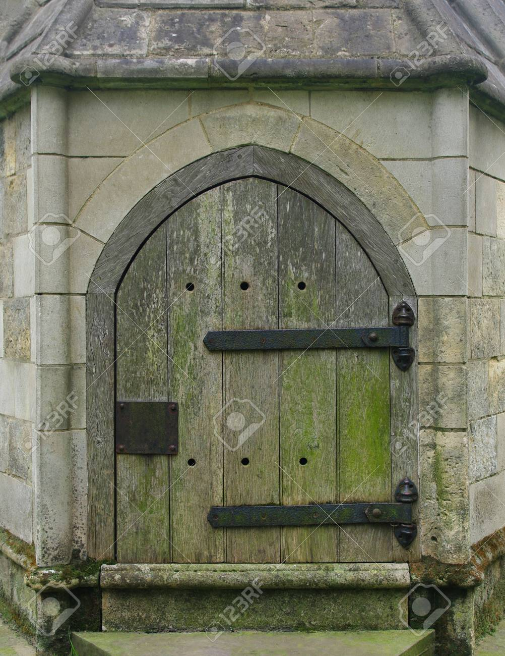 A small wooden Gothic door with large iron hinges in a stone wall. Stock & A Small Wooden Gothic Door With Large Iron Hinges In A Stone ...
