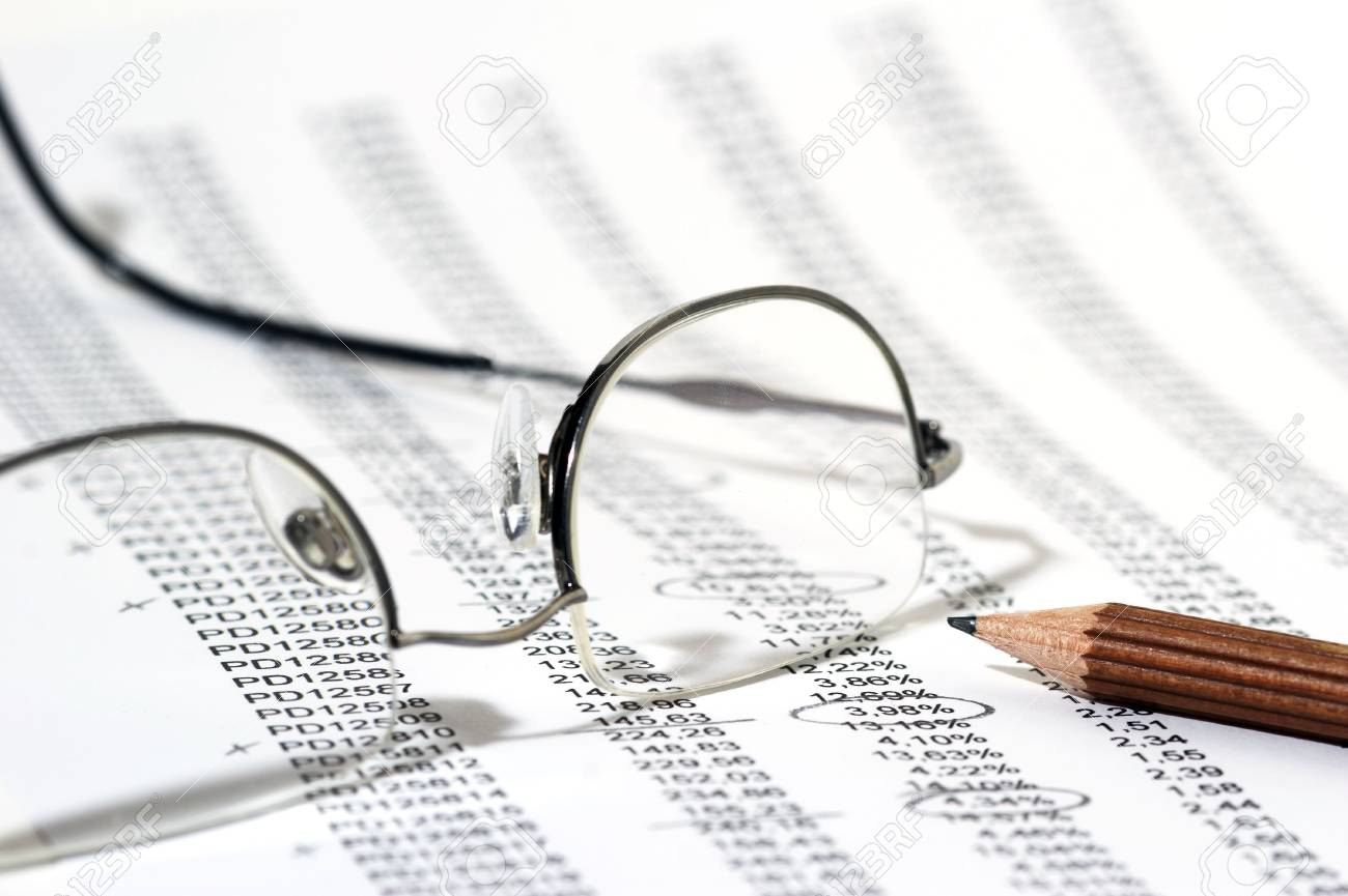 Sales Report in listform with marked data, brown pencil and eyeglasses Stock Photo - 724463