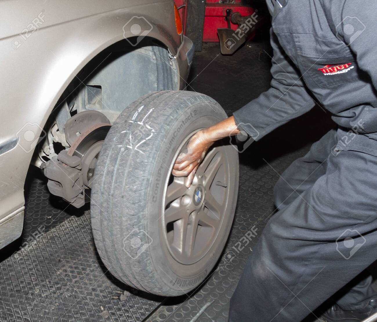 Checking spare tyre in boot of BMW at workshop - 152894278