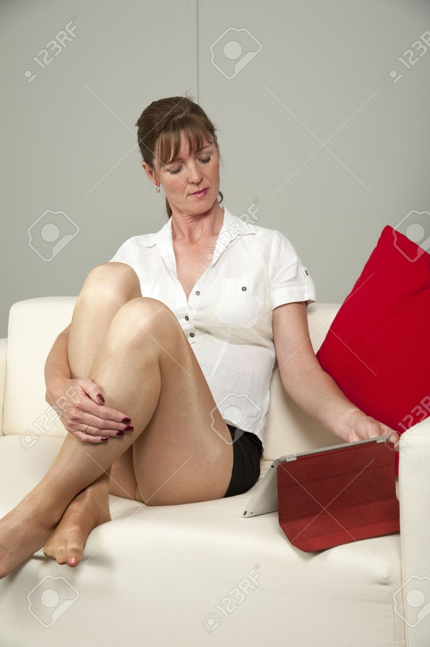 Woman Wearing Short Skirt Sitting On A Sofa Stock Photo, Picture ...