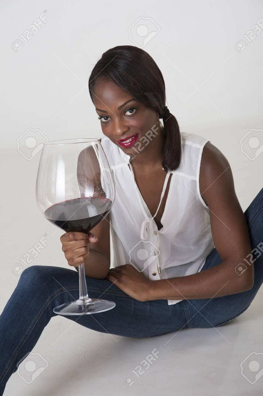 Jeune femme de dégustation de vin rouge à partir d'un grand verre
