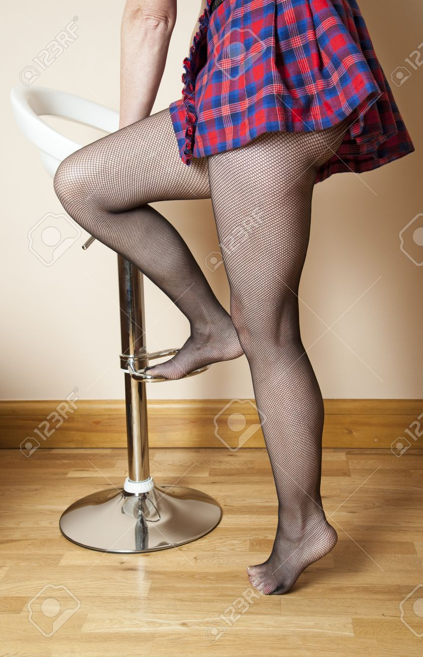 4bef9b837be92 Woman wearing fishnet tights getting onto a bar stool Stock Photo - 24535190