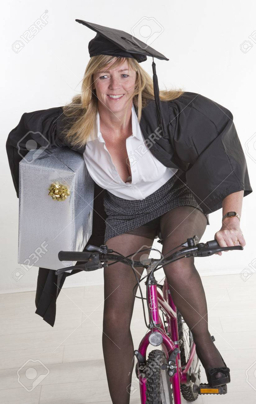 mature student in cap gown holding present riding cycle stock photo