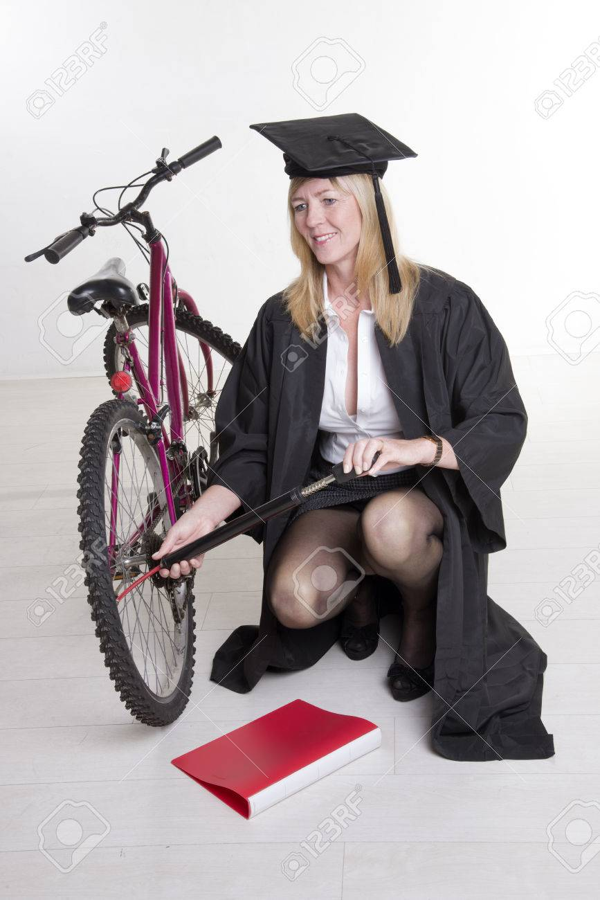 University Student In Cap And Gown Pumping Tire Of Her Bicycle Stock ...