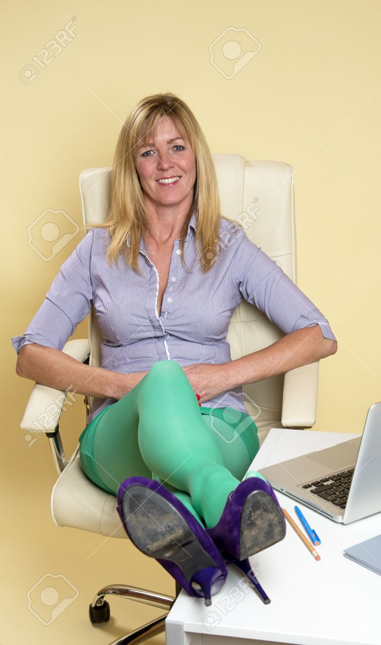 secretary sitting on office chair relaxing with legs on desk stock