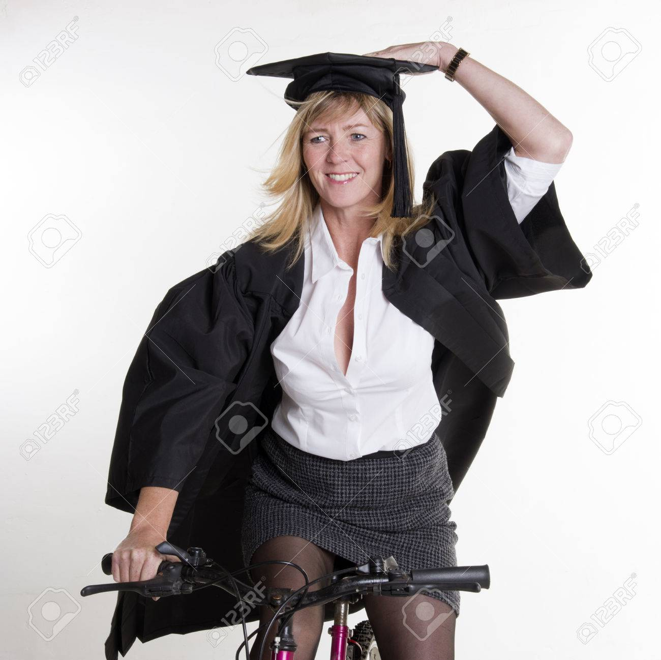 mature female student riding a bicycle wearing cap and gown stock