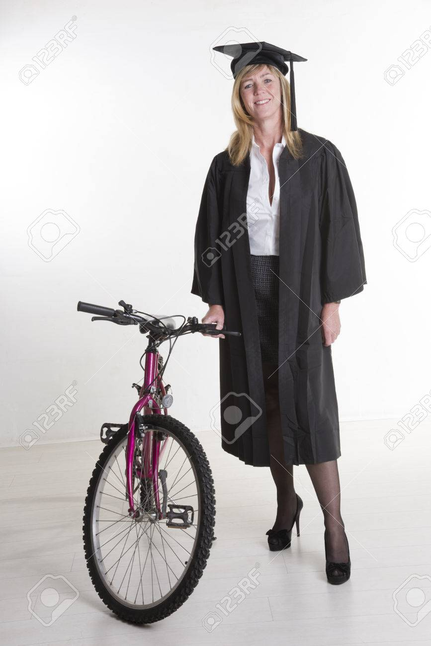 Mature University Student In Cap And Gown With Her Bicycle Stock ...