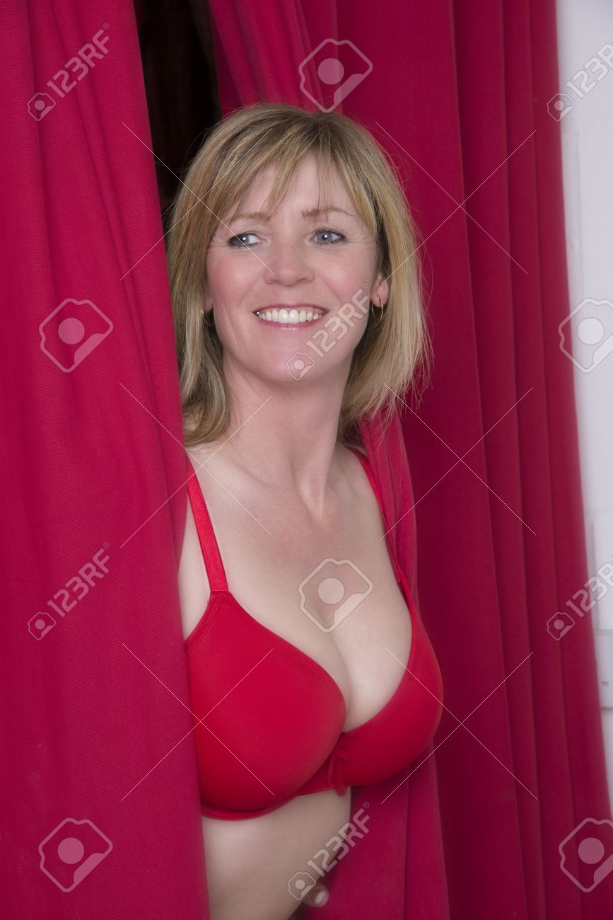 Stock Photo - Woman in red bra peering through a red curtain