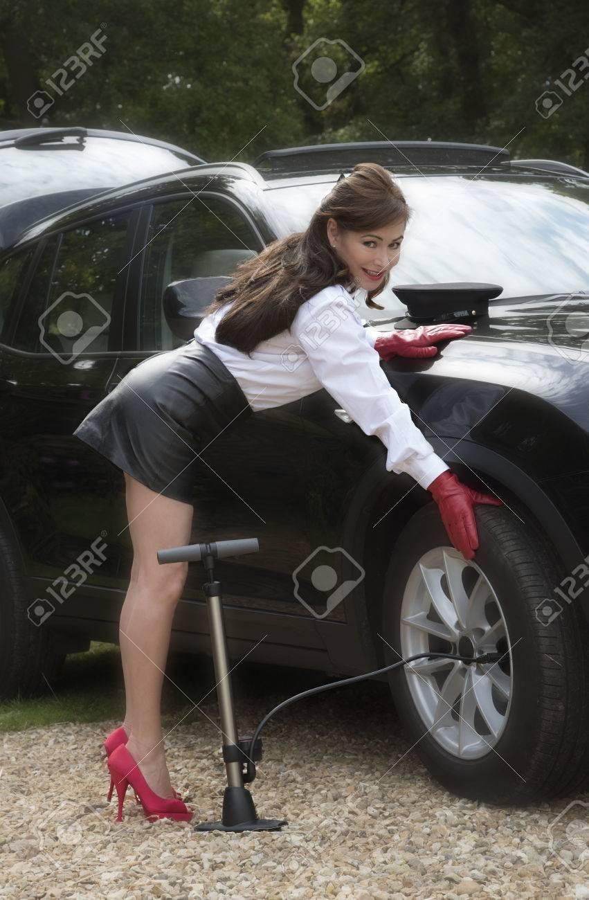 47457704-woman-chauffeur-checking-tyre-p