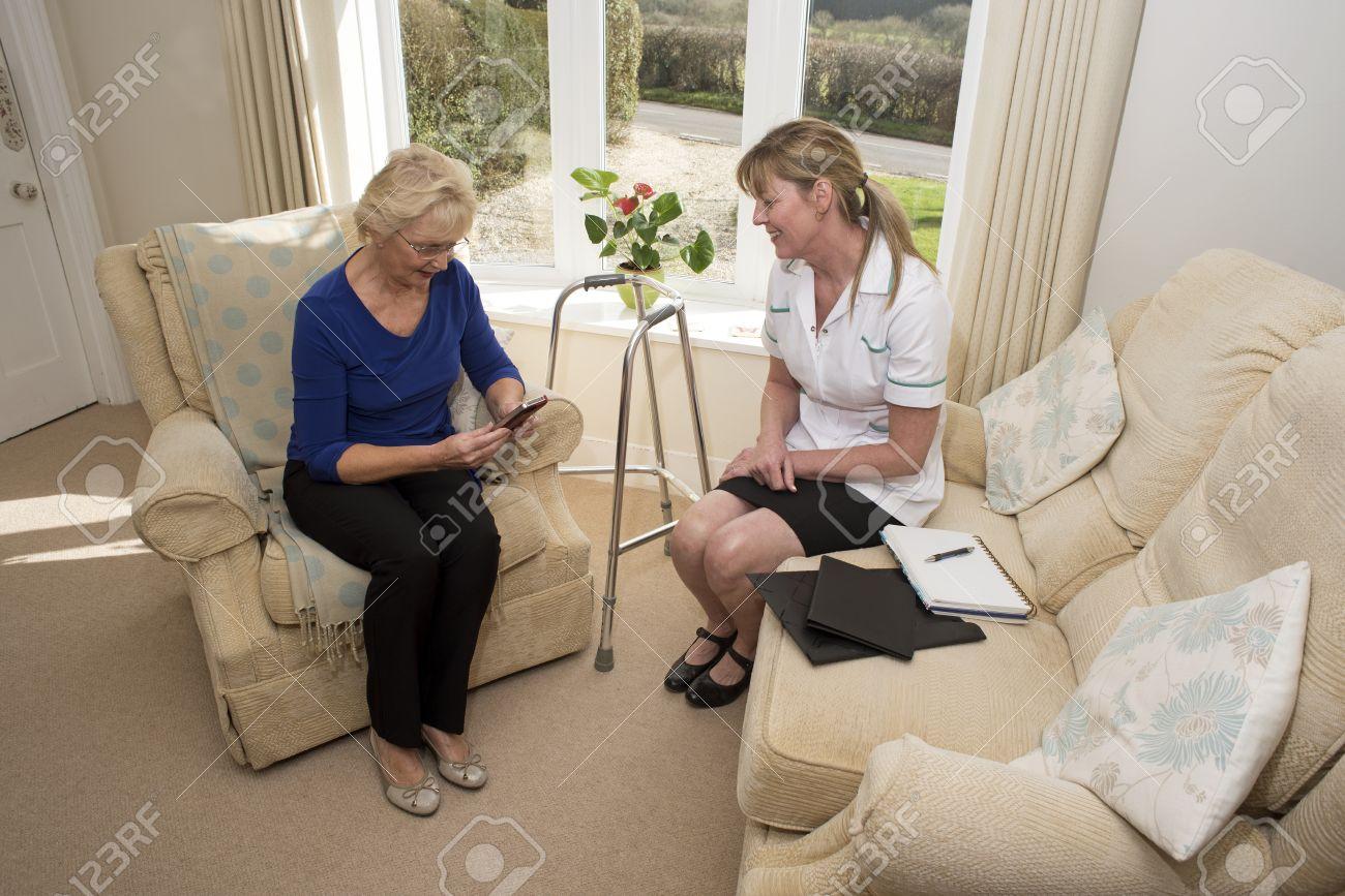 Infirmière sur une visite à domicile parler avec une patiente âgée