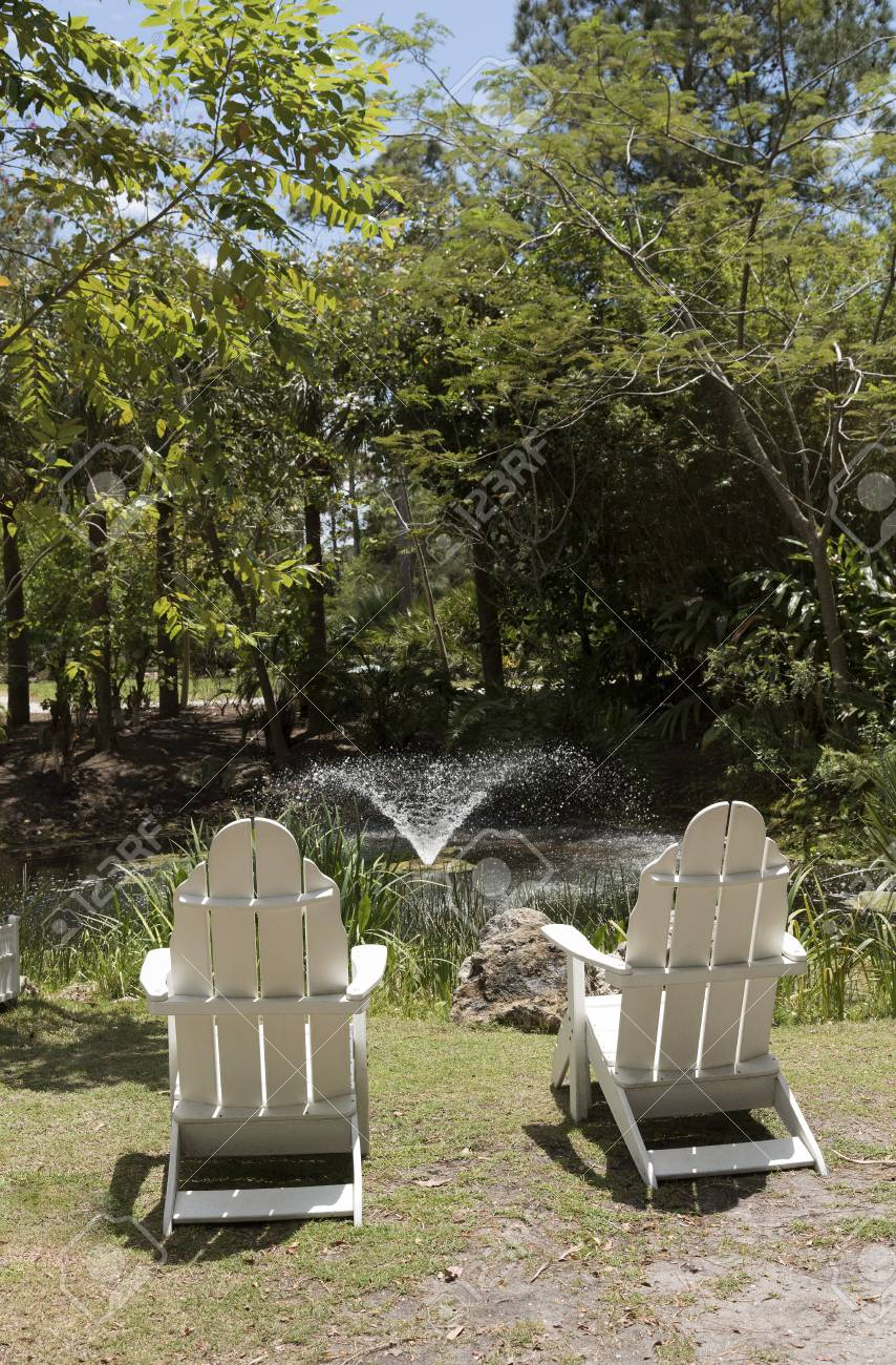 Adirondack Chair Sedie Da Giardino.Apair Of Adirondack White Wooden Chairs By A Garden Pond