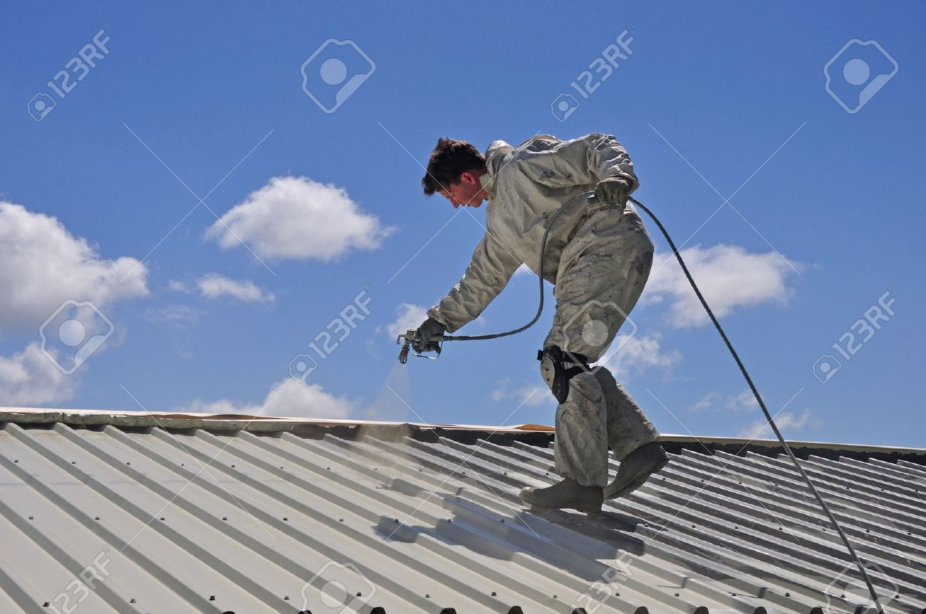 A trademan uses an airless spray to paint the roof of a building Stock Photo - 17277888