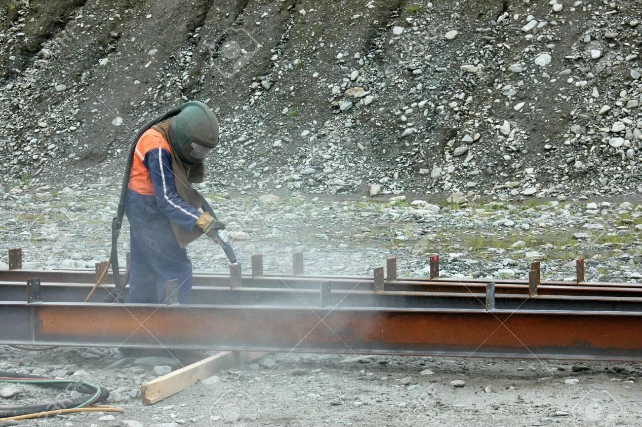 tradesman sandblasting beams for building project - 23339172