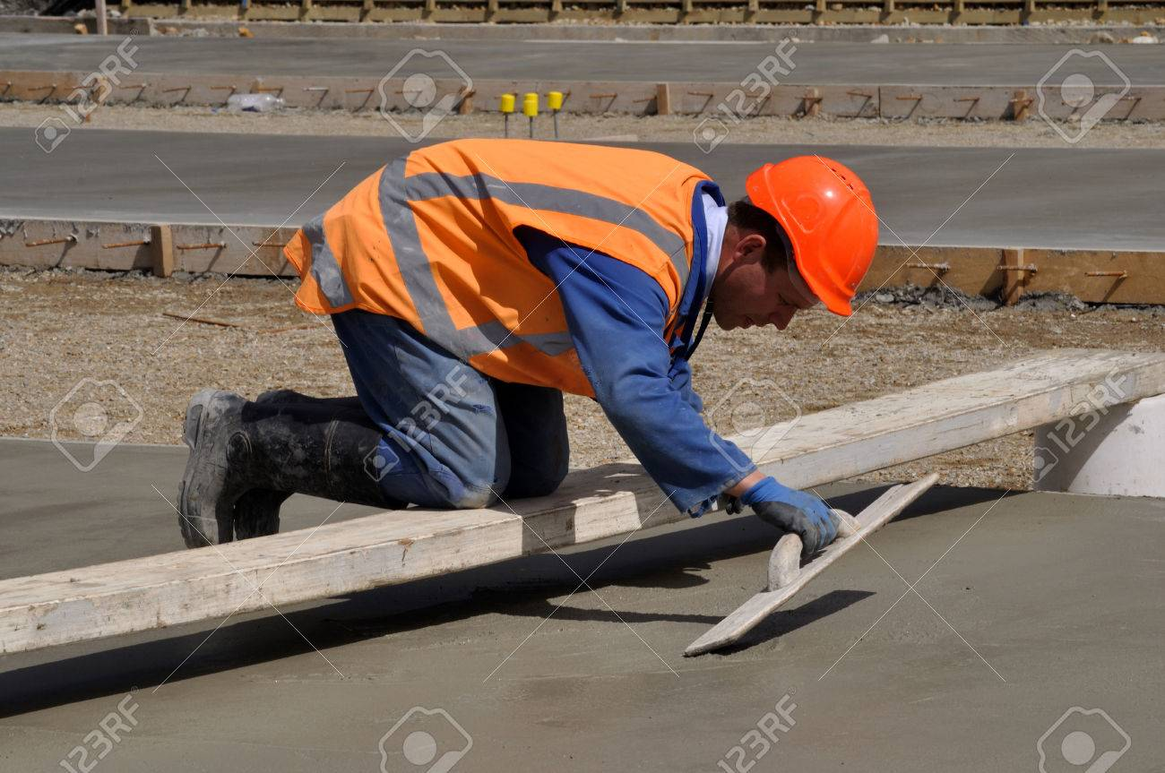 A Builder Uses A Wooden Trowel To Float Off A Wet Concrete Slab