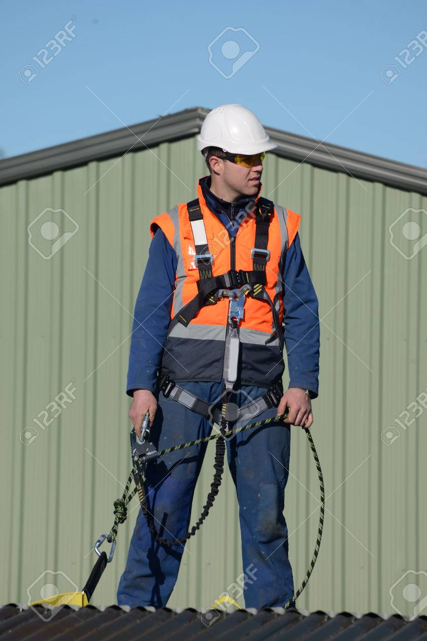A Builder Wearing Safety Harness While Working At Heights Waits For Instructions From The Foreman