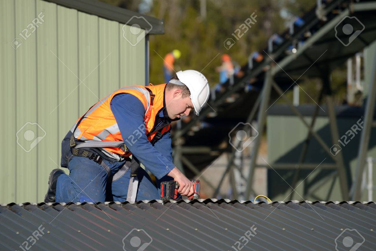 A Builder Wearing A Safety Harness For Working At Heights Unscrews Roofing  Iron On A Building
