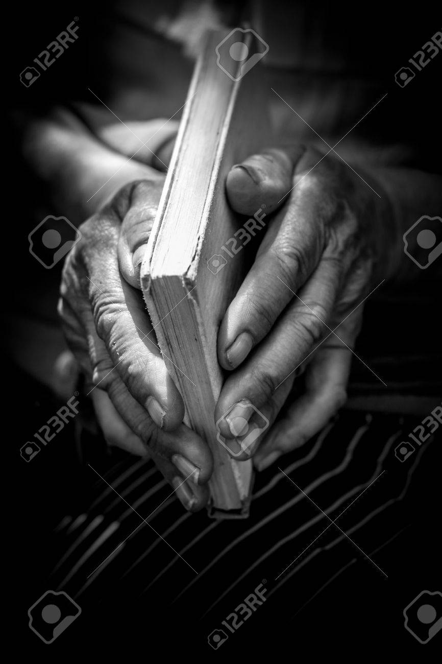 Old Woman Holding An Little Bible Or Book Black And White Stock Photo