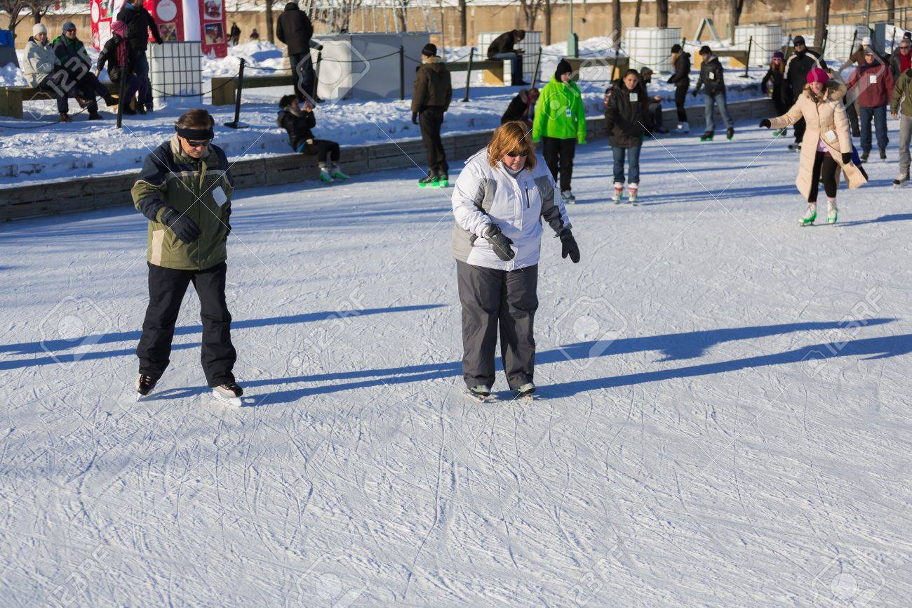 An Overweight Woman And And Elder Are Trying To Learn How To Ice Skate In A