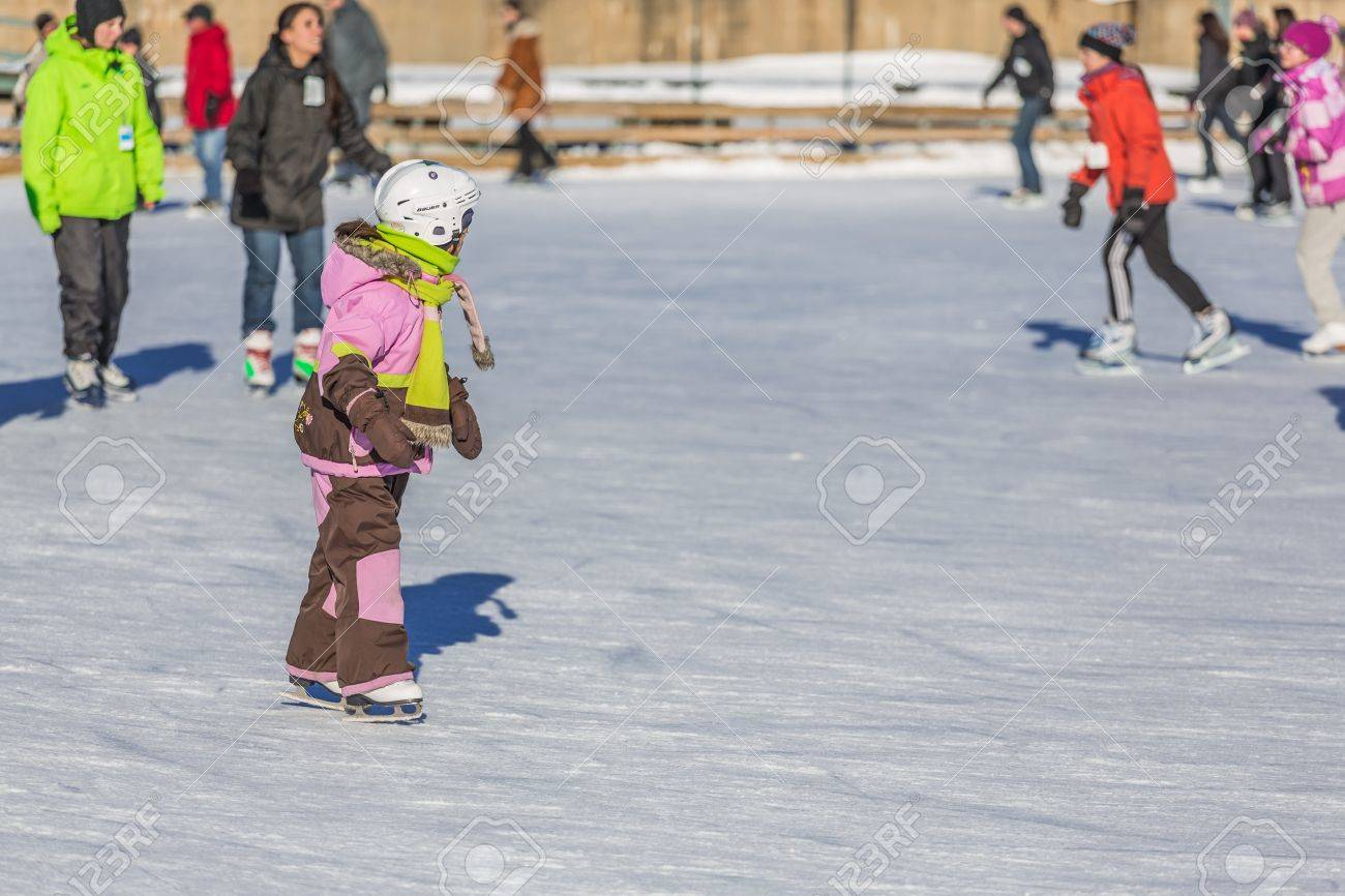 A Young Child Is Learning With Joy How To Ice Skate In A Really Cold Winter