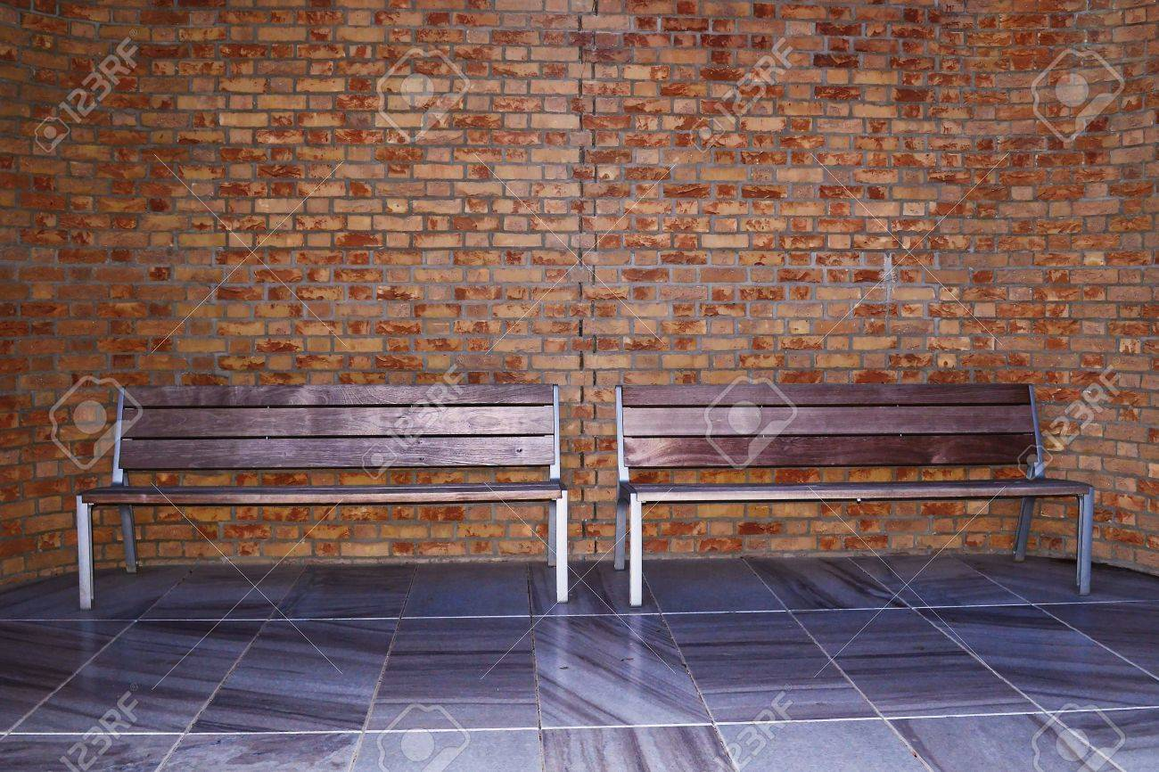 sidewalk scene with wooden bench and brick wall - 27559763