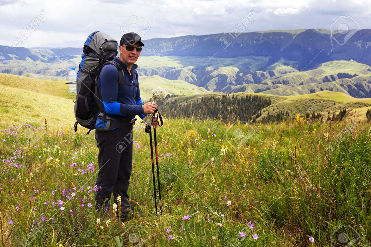 Hiker stopping to smell the wildflowers Stock Photo - 12539947