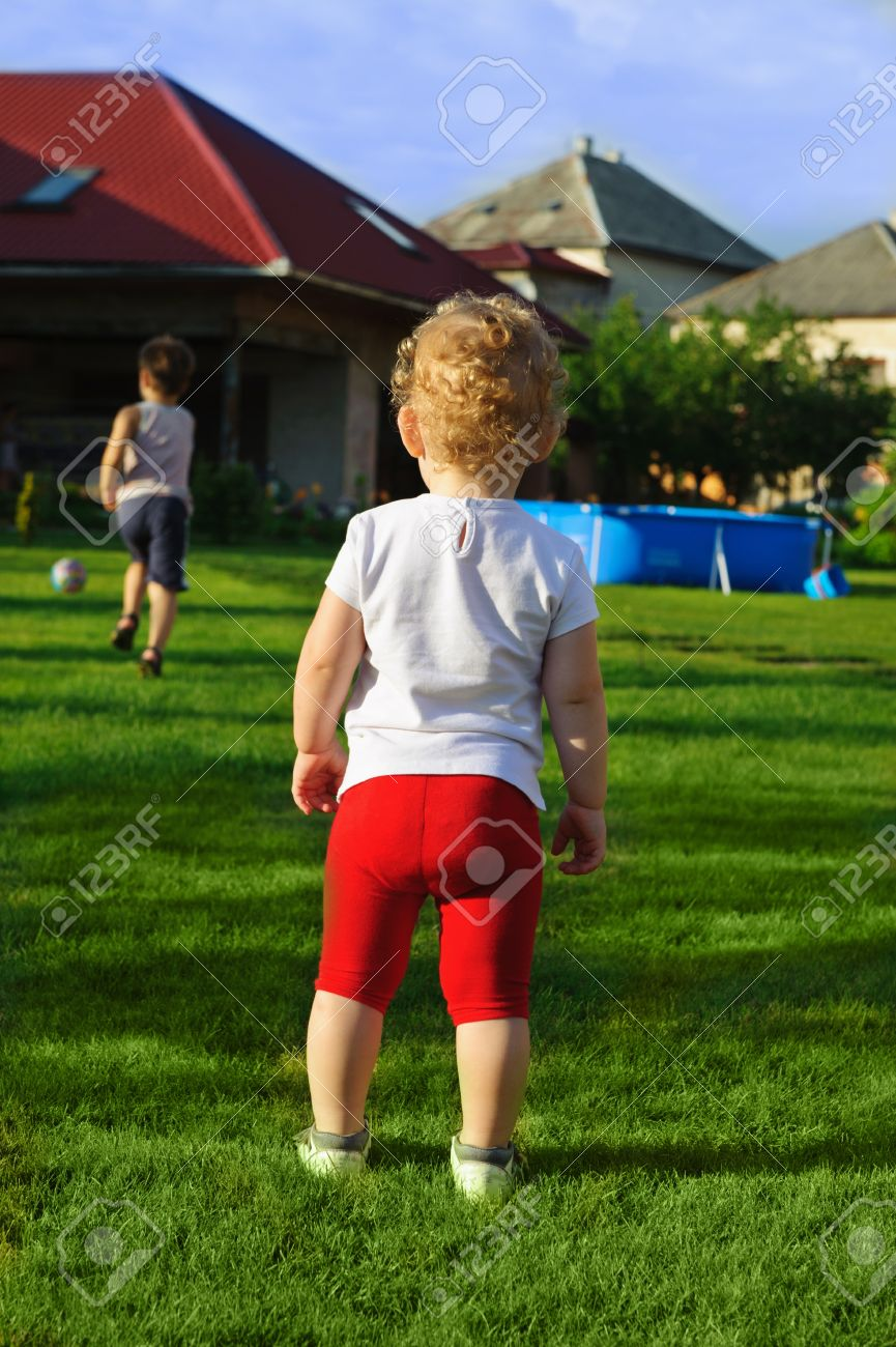 little and boy playing football on green grass at backyard