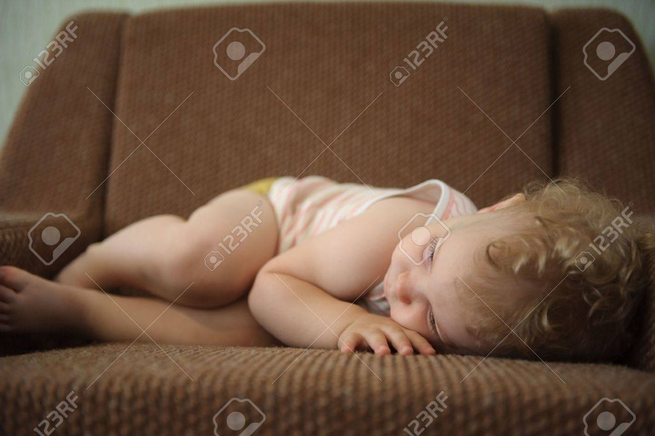 Curly haired blonde baby girl sleeping on armchair Stock Photo - 15214047