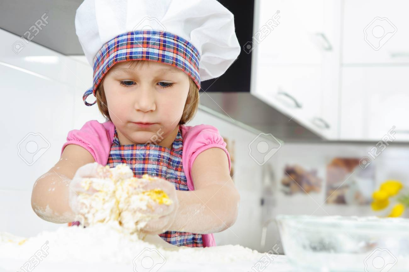 Cute little girl in hat and apron cooking cookies Stock Photo - 18118016