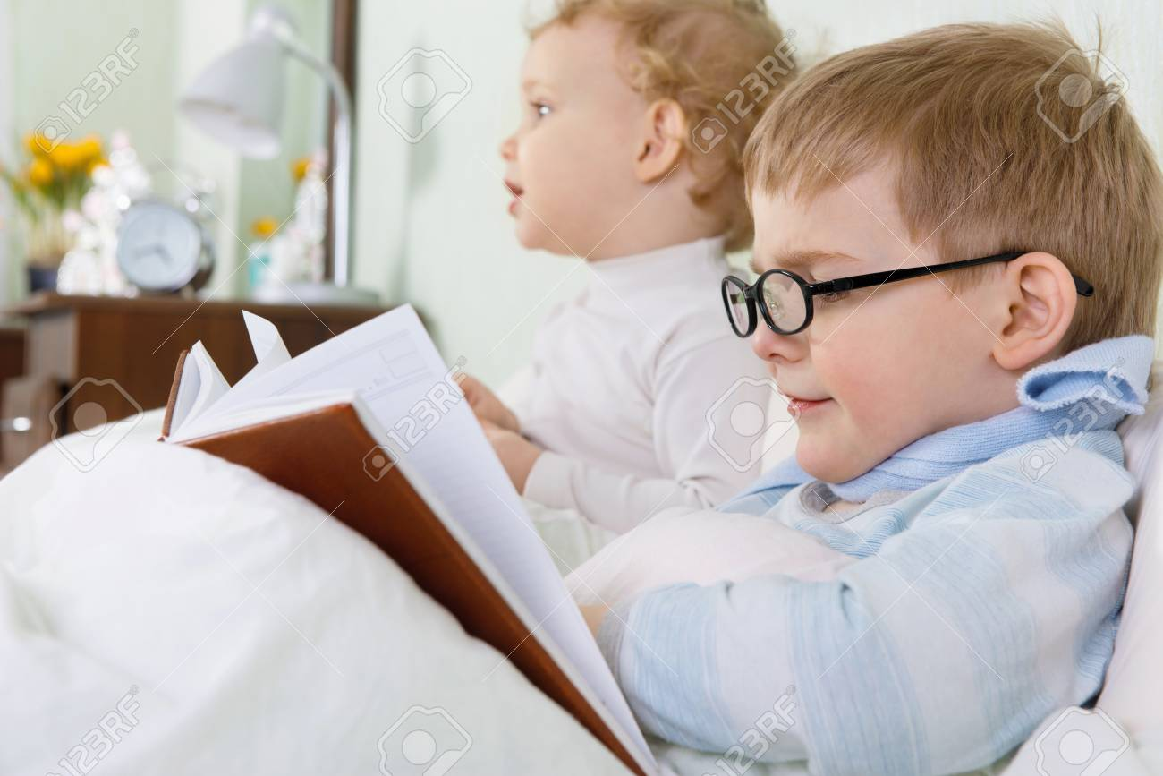 Little girl and her sick brother lying in bed at home Stock Photo - 18737048