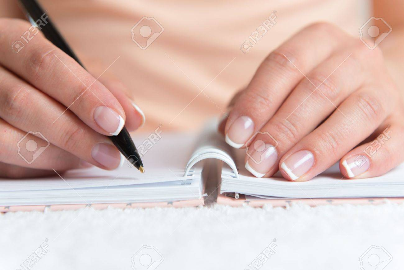 Young female is writing notes and planning her schedule Standard-Bild - 19608354
