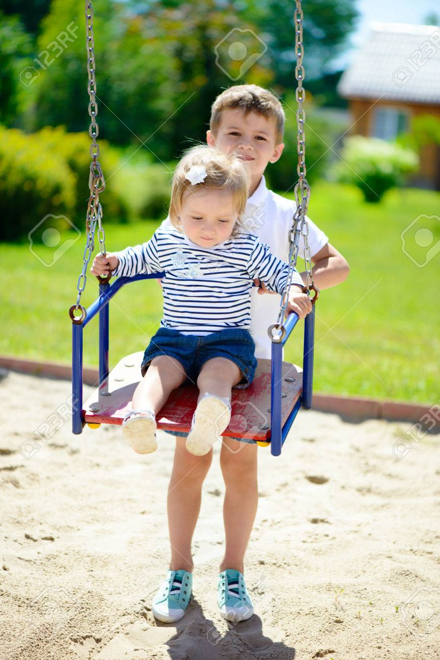 Little Cute Brother And Sister Swinging In Summer Park Stock Photo