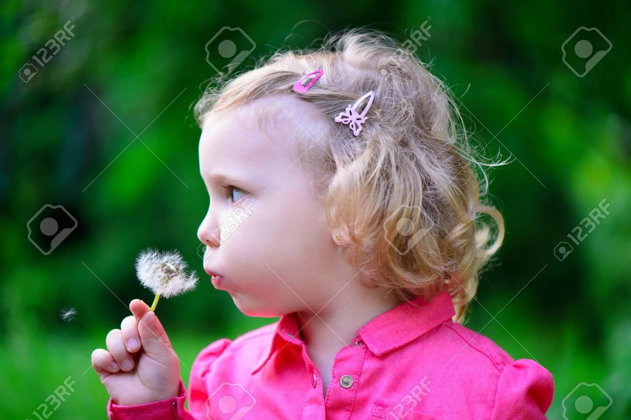 Cute little girl blowing dandelion in park Stock Photo - 29038783