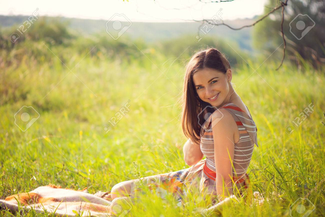 Elegant young smiling woman posing in sunny park - 41791565