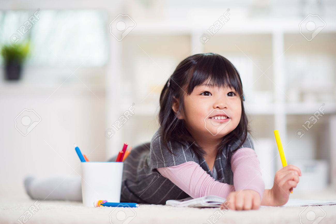 Pretty happy little japanese girl lying and drawing with pencils on white capet at home - 70370635