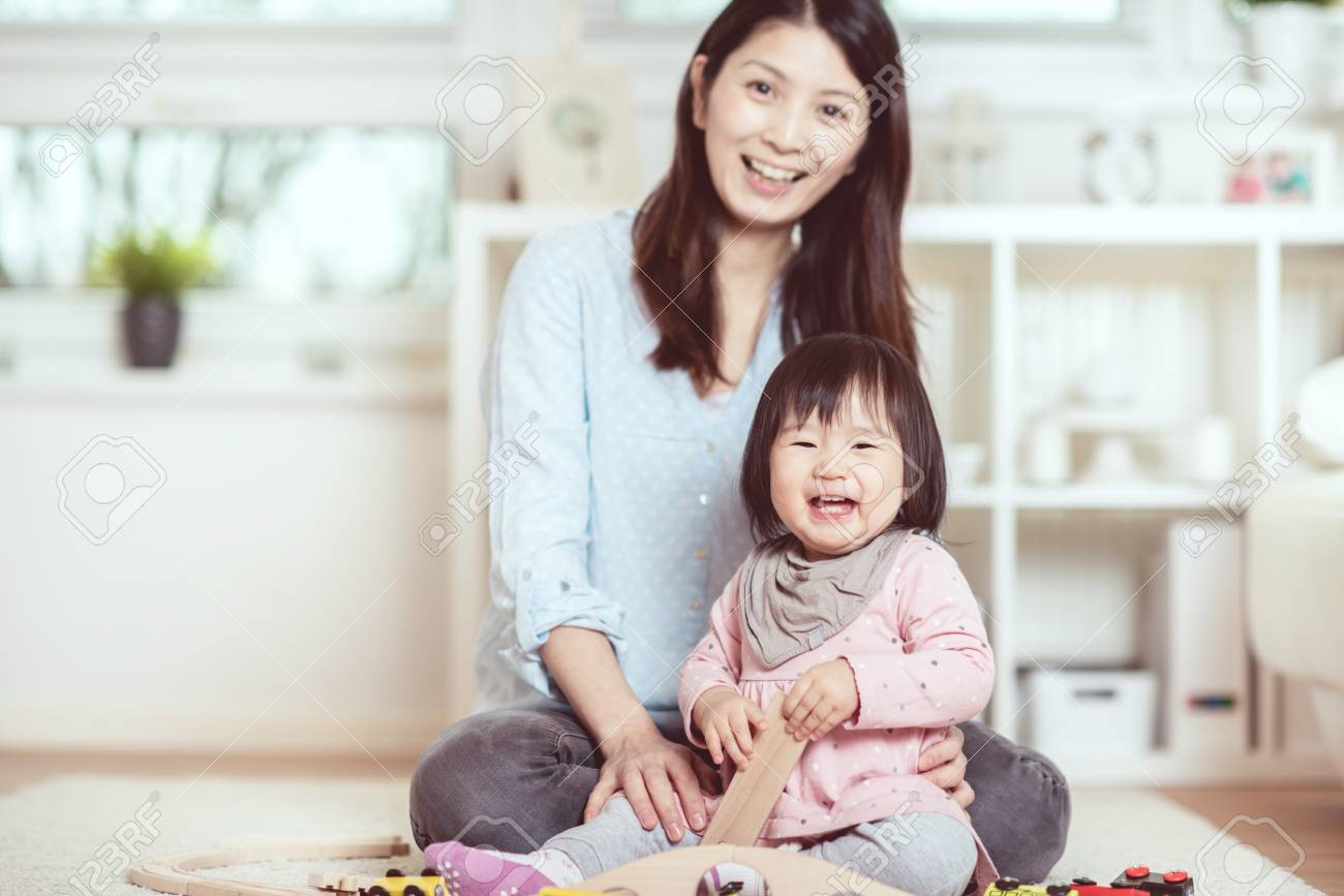 Pretty japanese woman playing with her cute laughing baby girl on the floor at home - 94517153