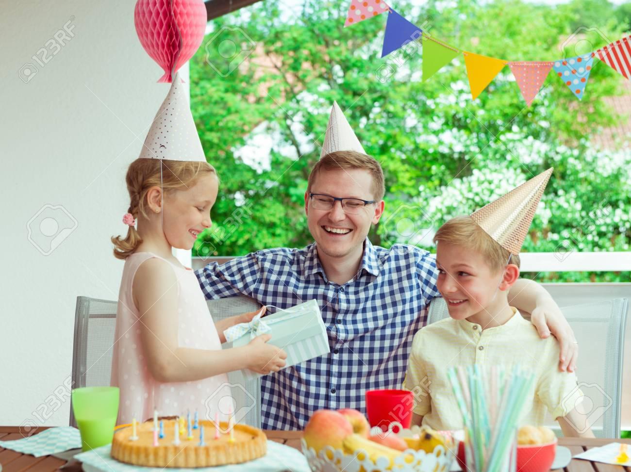Retrato De Feliz Joven Familia Celebrar Cumpleaños En La Terraza Muy Decorada