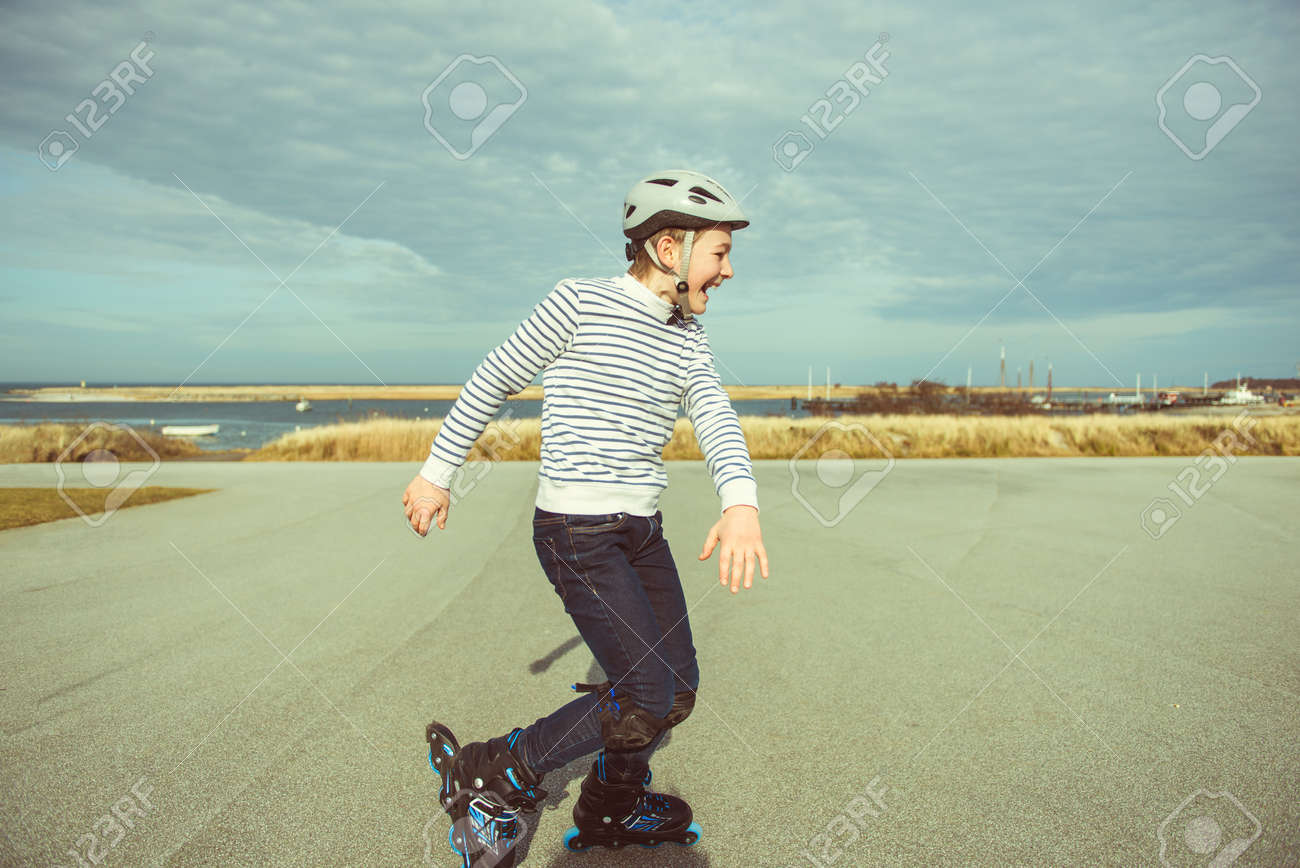 Happy teenager boy in helmet, inline skates and safety equipment is happy learning skating sunny day in summer - 165003120