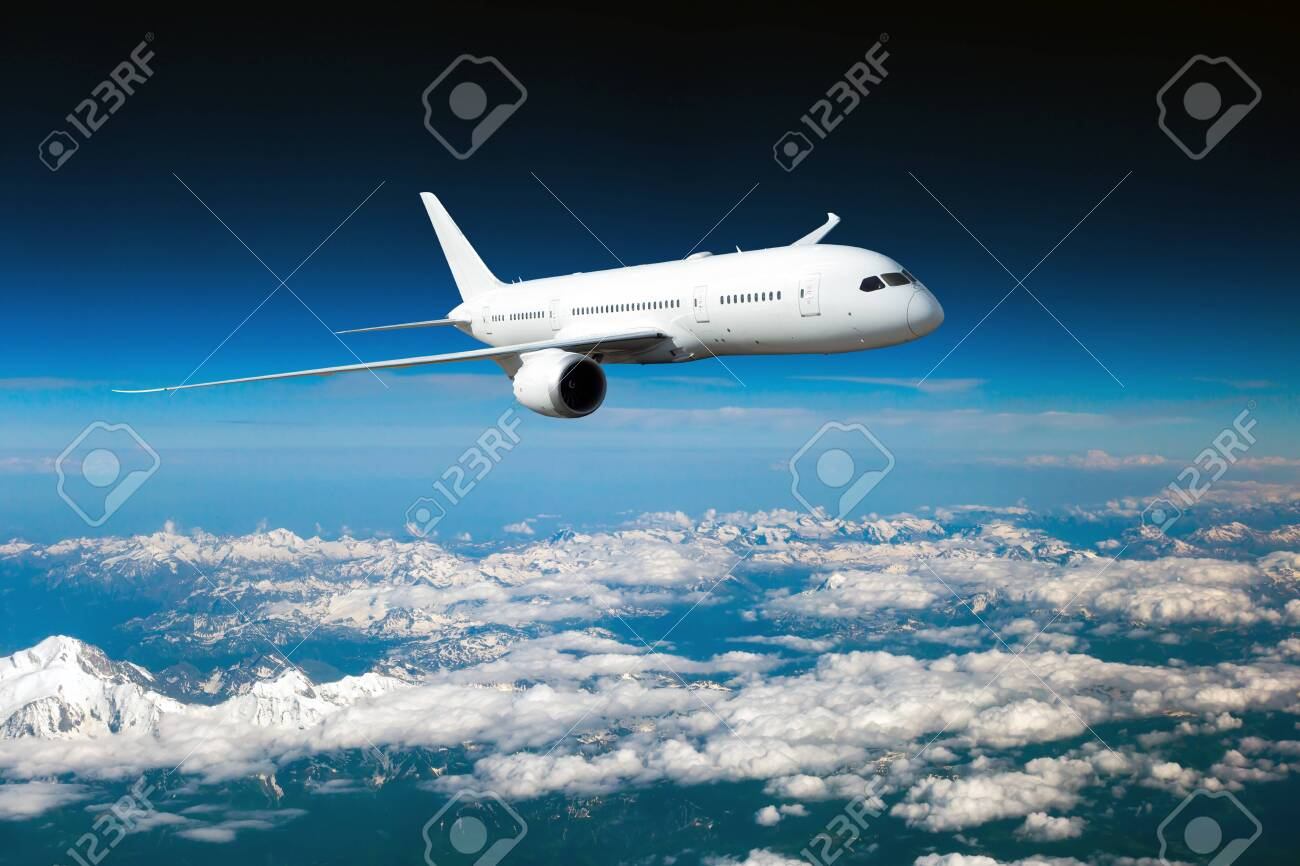 White passenger plane in flight. The plane flies above a snow covered mountain landscape. Aircraft front view. - 133798832