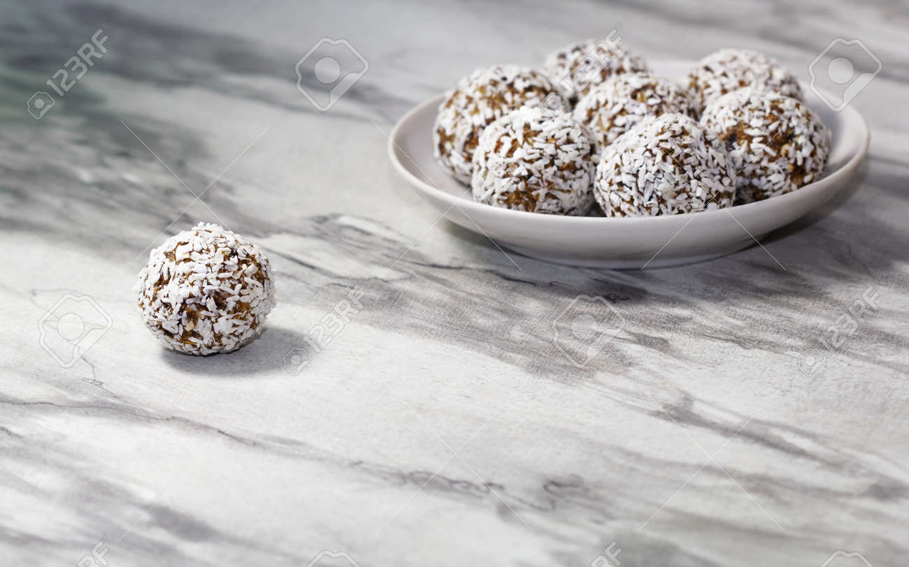 Homemade energy balls with dried apricots, raisins, dates, prunes, walnuts and coconut. Healthy sweet food. Energy balls in a plate on a marble gray background. Close up. Side view. Copy space - 170430090
