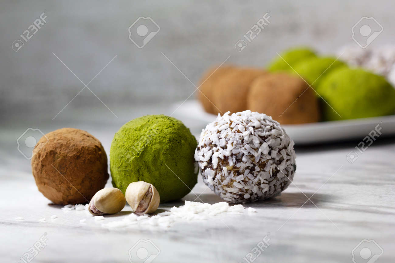Homemade energy balls with dried apricots, raisins, dates, prunes, walnuts, pistachios, green matcha, cacao and coconut. Assortment. Healthy sweet food. Energy balls in a plate on a marble background. - 170430107
