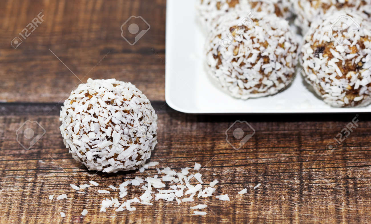 Homemade energy balls with dried apricots, raisins, dates, prunes, walnuts and coconut. Healthy sweet food. Energy balls in a plate on a wooden background. Close up. Side view. Copy space - 170430108