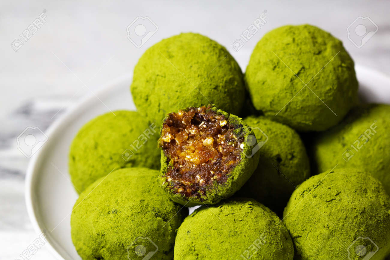 Homemade energy balls with dried apricots, raisins, dates, prunes, walnuts, pistachios and green matcha. Healthy sweet food. Energy balls in a plate on a marble gray background. Close up. Side view. - 170430113