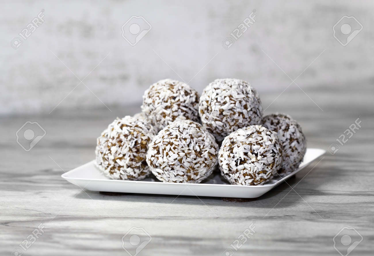 Homemade energy balls with dried apricots, raisins, dates, prunes, walnuts and coconut. Healthy sweet food. Energy balls in a plate on a marble gray background. Close up. Side view. Copy space - 170430146