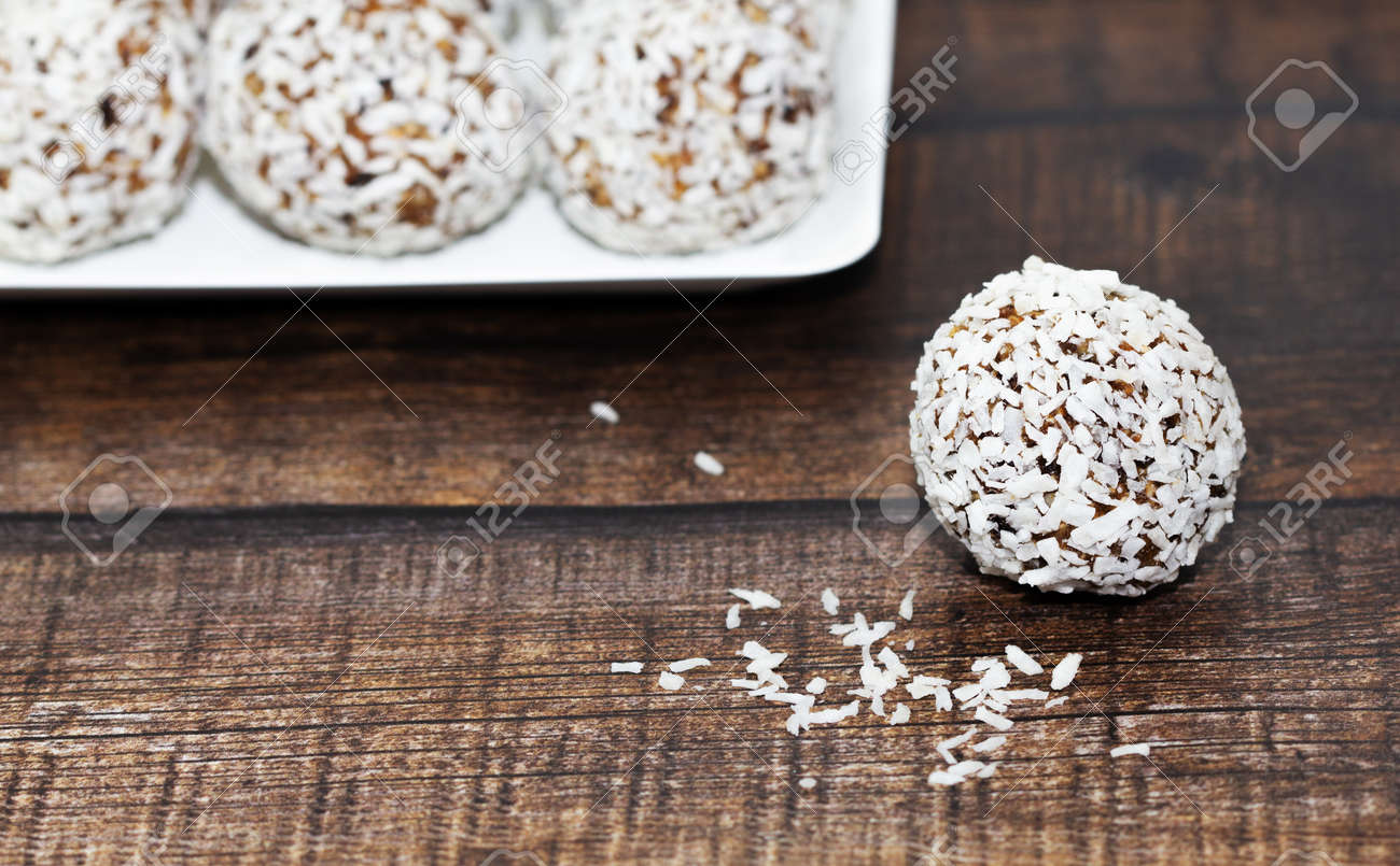 Homemade energy balls with dried apricots, raisins, dates, prunes, walnuts and coconut. Healthy sweet food. Energy balls in a plate on a wooden background. Close up. Side view. Copy space - 170430160