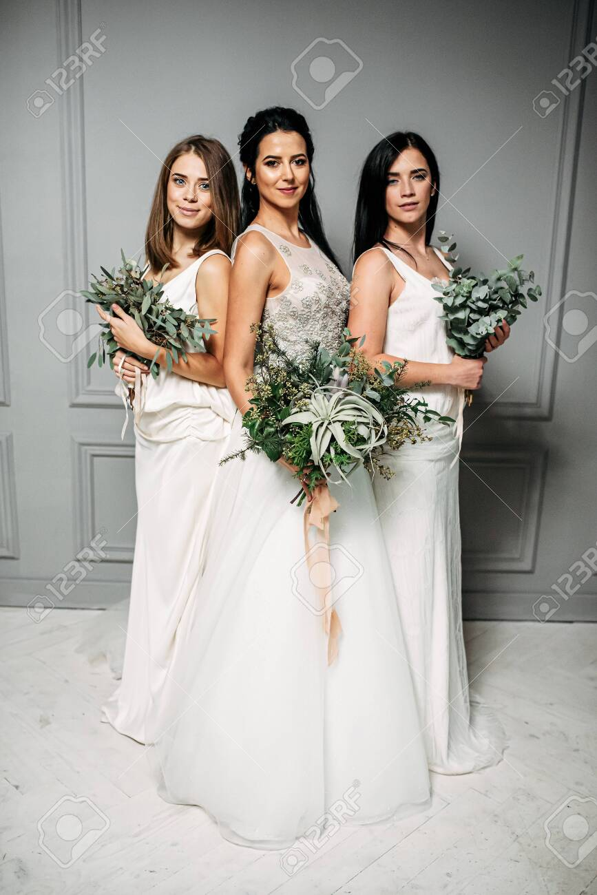 Friendship of women. Bride and bridesmaid three together. They have bouquets of green branches of eucalyptus and other plants in their hands. - 142571939